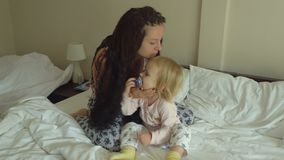 Mother and little daughter on the bed stock footage