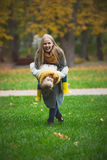 Mother and little daughter blonde with Teddy bear have fun and playing on green grass in autumn park Stock Image