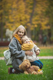 Mother and little daughter blonde with Teddy bear seating on green grass in autumn park, close up Royalty Free Stock Photos