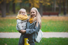 Mother and little daughter blonde with Teddy bear seating on green grass in autumn park, close up Stock Photography