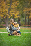 Mother and little daughter blonde with Teddy bear seating on green grass in autumn park Royalty Free Stock Photos