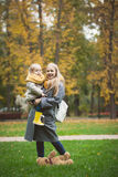 Mother and little daughter blonde with Teddy bear standing on green grass in autumn park Stock Photography