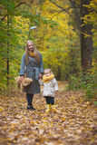 Mother and little daughter blonde walking and playing in autumn park, yellow lives around Royalty Free Stock Photos