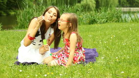 Mother with little daughter blowing a soap bubbles outdoor Stock Photos