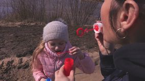 Mother and little daughter blowing up soap bubbles in the park stock video