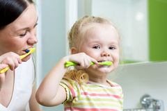 Mother and little daughter brushing teeth in bathroom Stock Photos