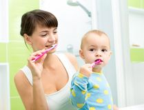 Mother and little daughter brushing teeth in Stock Image