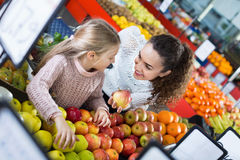 Mother and little daughter choosing seasonal fruits Stock Photos