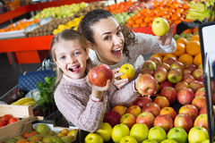 Mother and little daughter choosing seasonal fruits Royalty Free Stock Image