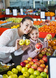 Mother and little daughter choosing seasonal fruits Stock Images
