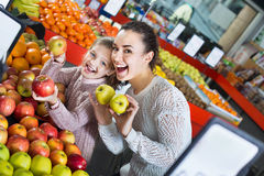 Mother and  little daughter choosing seasonal fruits Royalty Free Stock Photos
