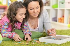 Mother with little daughter collecting  puzzle Royalty Free Stock Photos