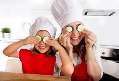 Mother and little daughter in cook hat and apron playing with cucumber slices on eyes in kitchen. Happy mother and little daughter wearing cook hat and red apron Stock Images