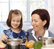 Mother and little daughter cooking Stock Images