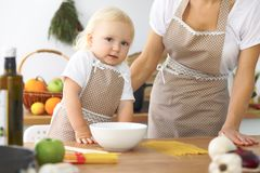 Mother and little daughter are cooking in the kitchen. Spending time all together or happy family concept.  Royalty Free Stock Photo