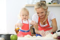 Mother and little daughter are cooking in the kitchen. Spending time all together or happy family concept.  Stock Photos