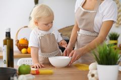 Mother and little daughter  cooking in the kitchen. Spending time all together or happy family concept.  Royalty Free Stock Images