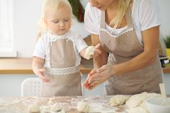 Mother and little daughter are cooking in the kitchen. Spending time all together or happy family concept.  Stock Images