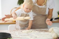 Mother and little daughter are cooking in the kitchen. Spending time all together or happy family concept.  Stock Image