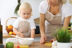 Mother and little daughter are cooking in the kitchen. Spending time all together or happy family concept.  Royalty Free Stock Images