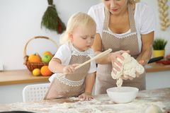 Mother and little daughter are cooking in the kitchen. Spending time all together or happy family concept.  Royalty Free Stock Photography
