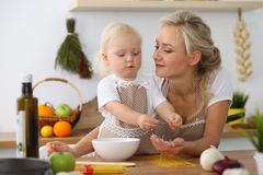 Mother and little daughter  cooking in the kitchen. Spending time all together or happy family concept.  Stock Photography