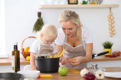 Mother and little daughter  cooking in the kitchen. Spending time all together or happy family concept.  Stock Images