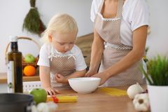 Mother and little daughter  cooking in the kitchen. Spending time all together or happy family concept.  Stock Photos