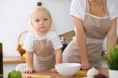 Mother and little daughter  cooking in the kitchen. Spending time all together or happy family concept.  Royalty Free Stock Photo