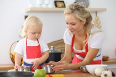 Mother and little daughter  cooking in the kitchen. Spending time all together or happy family concept.  Royalty Free Stock Photos