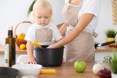 Mother and little daughter  cooking in the kitchen. Spending time all together or happy family concept.  Stock Image
