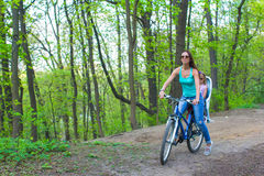 Mother and little daughter cycling bicycle at the park Royalty Free Stock Photos