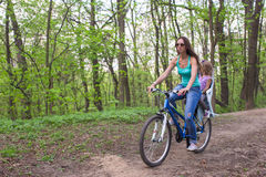 Mother and little daughter cycling bicycle at the park Royalty Free Stock Image