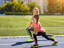 Mother and little daughter are doing exercise in the stadium. He Royalty Free Stock Images