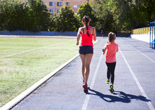 Mother and little daughter are doing exercise in the stadium. He. Mother and little daughter are doing exercise in the stadium. Family doing fitness at the Stock Photo