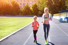 Mother and little daughter are doing exercise in the stadium. Family doing fitness at the stadium. Healthy family concept Royalty Free Stock Image