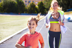 Mother and little daughter are doing exercise in the stadium. Family doing fitness at the stadium. Healthy family concept Stock Photo