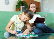 Mother with little daughter  doing homework Stock Photography