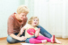 Mother with a little daughter drawing Stock Photography