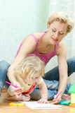 Mother with a little daughter drawing Stock Photos