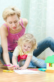 Mother with a little daughter drawing Royalty Free Stock Image