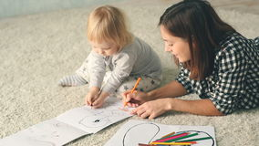 Mother with little daughter draws in album with pencils. Pretty young mother and cute little daughter are lying on the floor and drawing with pencils stock footage