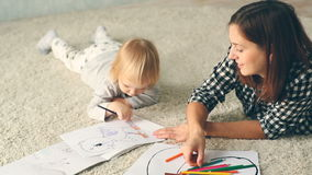 Mother with little daughter draws in album with pencils. Young mother and cute little daughter are lying on the floor and drawing with pencils. Little girl run stock video