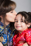 Mother with little daughter dressed in beautiful chinese blue and red dresses posing happily embracing for camera Royalty Free Stock Photos