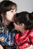 Mother with little daughter dressed in beautiful chinese blue and red dresses posing happily embracing for camera Royalty Free Stock Photo