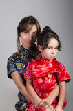 Mother with little daughter dressed in beautiful chinese blue and red dresses posing happily embracing for camera Stock Images