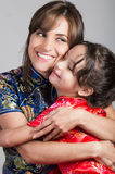 Mother with little daughter dressed in beautiful chinese blue and red dresses posing happily embracing for camera Stock Photography