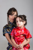 Mother with little daughter dressed in beautiful chinese blue and red dresses posing happily embracing for camera Stock Image