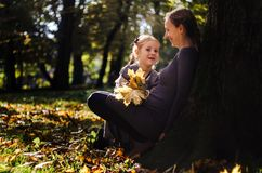 Mother with daughter in the autumn park. Mother with little daughter dressed in grey clothes walking in the autumn park Royalty Free Stock Photo
