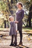 Mother with daughter in the autumn park. Mother with little daughter dressed in grey clothes walking in the autumn park Royalty Free Stock Photography